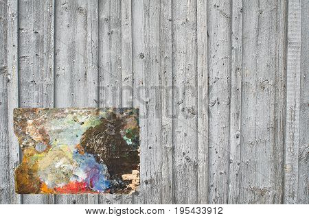 A fragment of a wall built from rhythmically spaced boards and battens with located on the background of the artist's palette.
