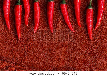 red hot chili peppers, popular spices concept - decorative arrangement of nine colorful pods of chili on brown background of dried powder of ground hot pepper, top view, flat lay, free space for text