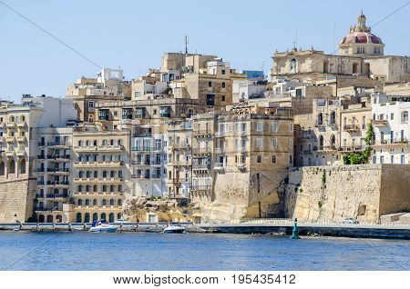 Senglea waterfront as seen from the Grand Harbour with the St. Philip's Chapel dome and buildings inside defensive walls. Senglea Malta.