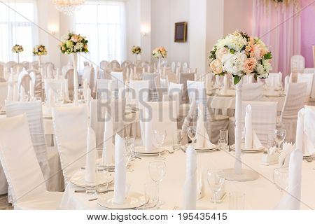 Restaurant interior for banquet, wedding decor. Glass, napkins and cutlery. Table appointments, laying.