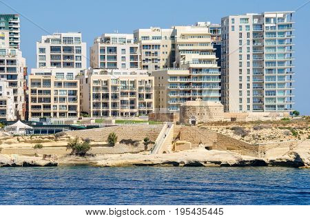 Tigne Point with Fort Tigne with its circular keep built by the Order of Saint John one of the oldest polygonal forts in the world and modern residential buildings in Sliema Malta
