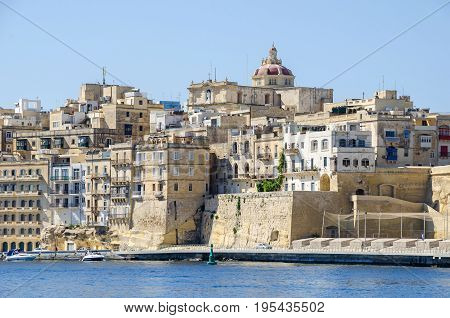 Senglea, Malta- June 4 2017: Senglea waterfront as seen from the Grand Harbour with the St. Philip's Chapel dome and buildings inside of defensive walls