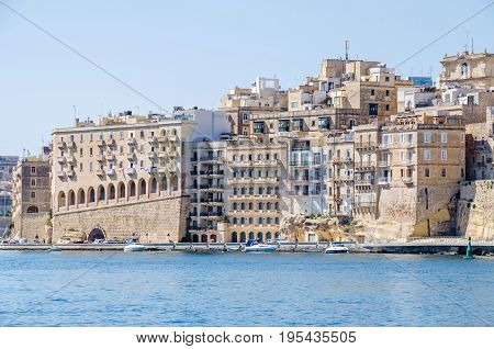 Senglea, Malta- June 4 2017: Senglea waterfront as seen from the Grand Harbour its modern part with buildings adapted to the old maltese architectural style