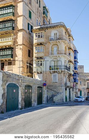 Valletta Malta - June 4 2017: Marsamxett Street with the typical residential buildings constructed with Maltese limestone and colorful windows and balconies