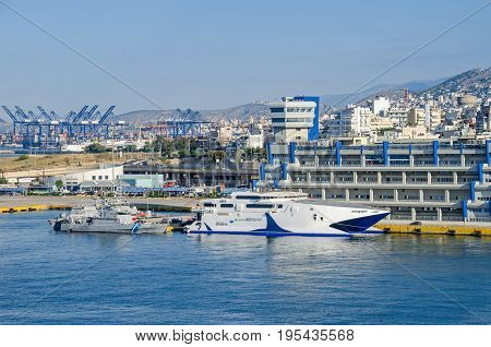 Port of Piraeus Greece - Mai 30 2017: Ministry of Mercantile Marine building with ferry boat operated by Atlanticoline and coast guard boat anchored at it with cranes of commercial port in the background