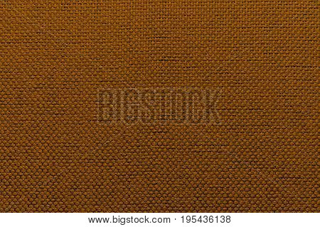 A fragment of fabric. Rugged textile brown background