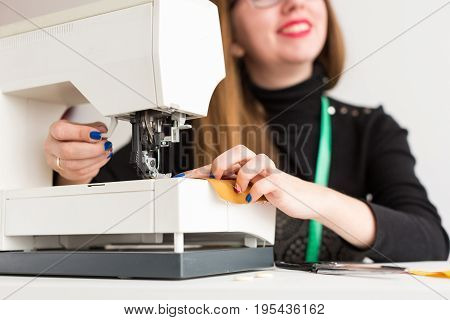 needlework and quilting in the workshop of a young woman, a tailor - a young girl with a smile on his face and a bright blue manicure sew on sewing machine, close-up done at the hands of a master