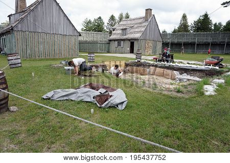 MACKINAW CITY, MICHIGAN / UNITED STATES - JUNE 18, 2017: Archaeologists dig for artifacts on the grounds of Fort Michilimackinac, in the Colonial Michilimackinac State Park.