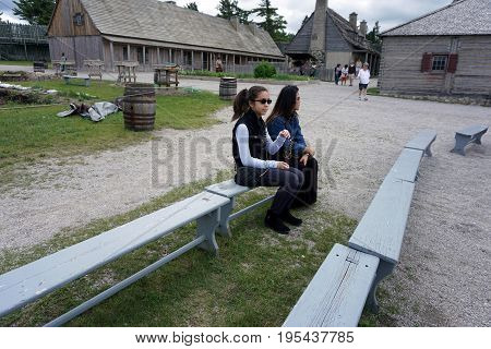 MACKINAW CITY, MICHIGAN / UNITED STATES - JUNE 18, 2017: Visitors enjoy sitting on a bench while visiting Fort Michilimackinac, in the Colonial Michilimackinac State Park.