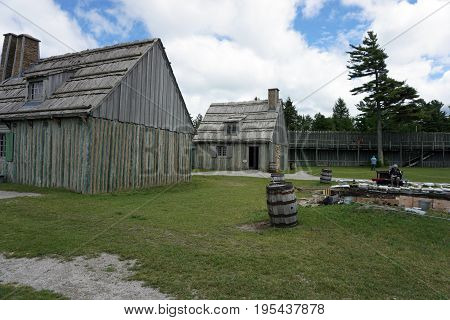 MACKINAW CITY, MICHIGAN / UNITED STATES - JUNE 18, 2017: Rowhouses stand beside an archaeological site on the grounds of Fort Michilimackinac, in the Colonial Michilimackinac State Park.
