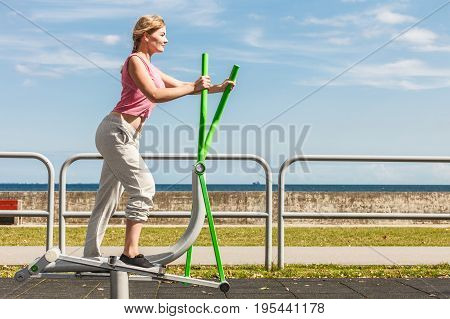Active Woman Exercising On Elliptical Trainer.