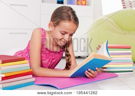 Young girl reading at home - lying on the floor with books on her side