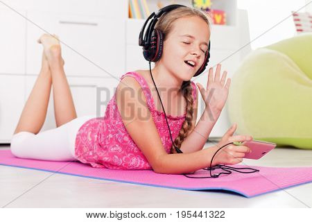 Young girl singing a tune listening to music on her phone - lying on the floor at home