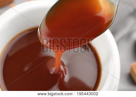 Pouring caramel sauce into bowl, closeup