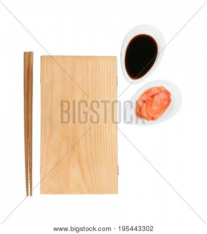 Wooden board, chopsticks, soy sauce and pickled ginger on white background