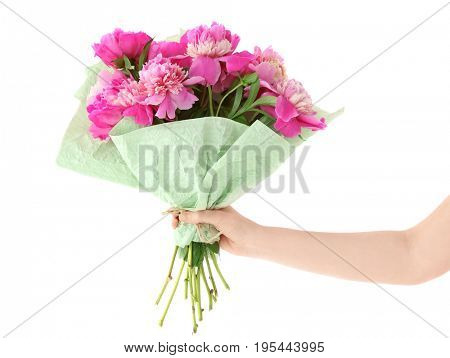 Female hand holding beautiful bouquet with fragrant peonies on light background