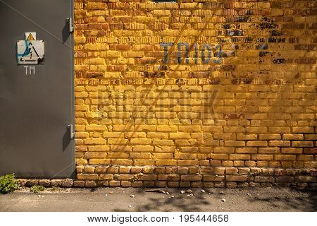 Vibrant yellow brick wall background with a door and a high voltage danger sign. Dirty grunge industrial backdrop with signs letters and numbers