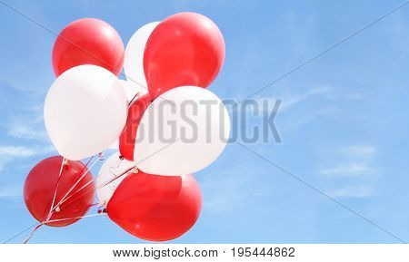 Red and white balloons against a blue sky.