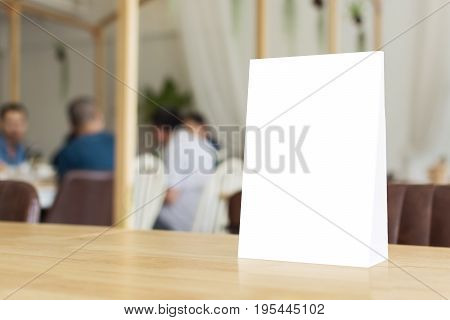 Mock up blank template menu frame on wood table in restaurant with blurred background Clipping path included