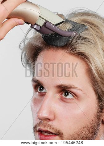 Hairdo hairstyle concept. Cool male hairstylist making self trendy haircut fashion blonde metrosexual model going to shave his long hair
