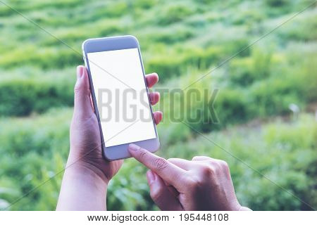 Mockup image of a hand holding pressing and using white smart phone with blank screen at outdoor and green nature background