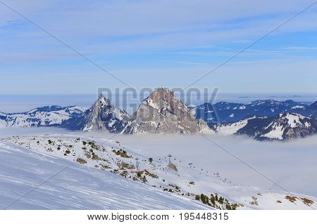 Wintertime view from Fronalpstock mountain in the Swiss canton of Schwyz, summits of Kleiner Mythen and Grosser Mythen mountains rising from sea of fog in the background.