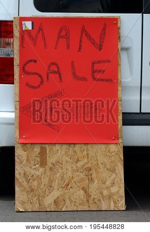 Humor arrow directional sign for Man Sale on red cardboard on placard