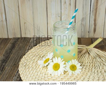 lemonade in polka dot mason jar with striped drinking straw and white daisies on bamboo place mat