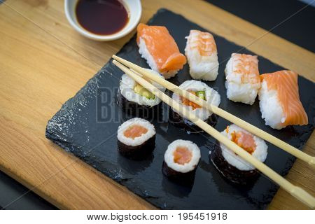 Rice, Sushi on a wooden table on black slate plate with soy sauce and chopsticks