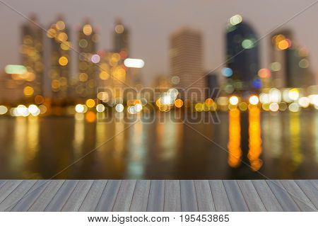 Opeing wooden floor City office building with water refleciton blurred bokeh light abstract background