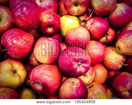 Red apples background. Fresh organic red apple stands out among many apples background in the market. Closeup shot of fresh red and yellow apple
