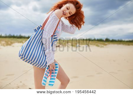 The redhead girl walks alone on the empty beach