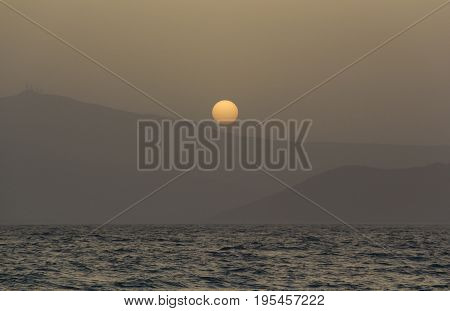 Beautiful dreamy sunset over Paros island mountains, a view through misty air from Naxos island.