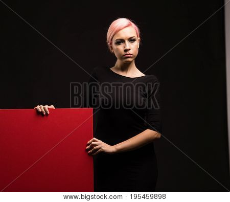 Young serious woman portrait of a confident businesswoman showing presentation, pointing placard black background. Ideal for banners, registration forms, presentation, landings, presenting concept.