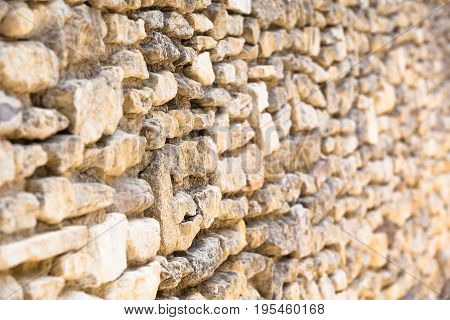 Closeup ancient natural wall of bright dry stones (focused and blurred part, copy space)