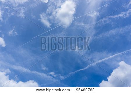 View on beautiful white Clouds on a Blue Sky.  Cloud Formations.  Natural Background.  Close-up of Contrails on a blue Sky.