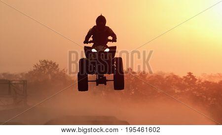 Silhouette ATV or Quad bikes Jump in the sunset .