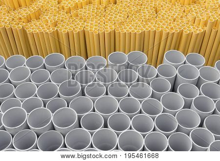 Gray and yellow PVC pipes stacked in warehouse.