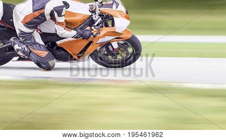 Motorcycle leaning into a fast corner on highway .