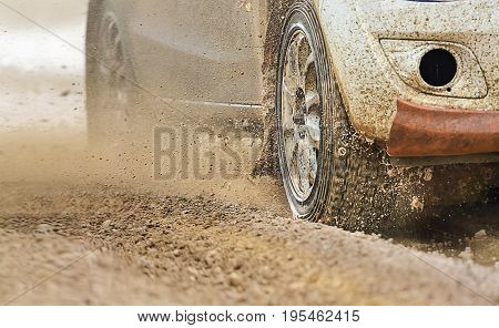 Rally car increase speed in muddy road  .