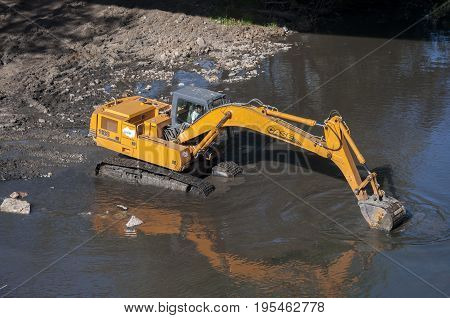 Backhoe working in the River Bernesga in La Pola de Gordon Leon Province Spain on July 14 2014.