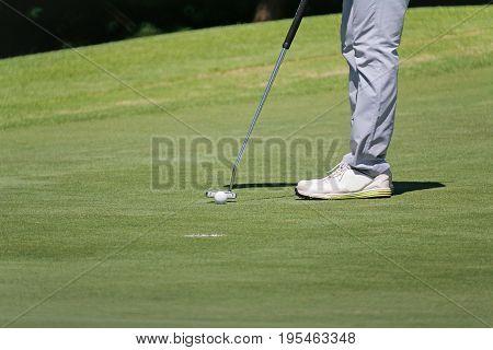 golfer putting, selective focus on golf ball