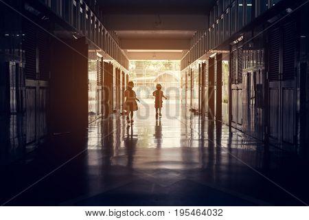 vintage tone silhouette image of kids running in school hall way.