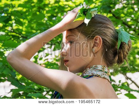 a young girl in a dress with nude backs worth in the foliage in the Woods hair decorated with foliage. in the sunlight.