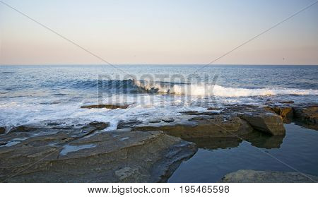 high cliff above the sea, the cliff descends into the sea, many splashing waves and stones. sunny day