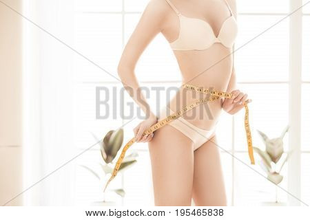 Young female weight loss perfect body holding tape measure