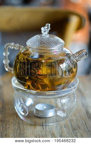 Glass kettle with blooming flower tea on wooden table. Stand with little candle. Bundle of flowering green tea inside teapot. Chinese tea making tradition. Blurred background. For cafe, restaurant.