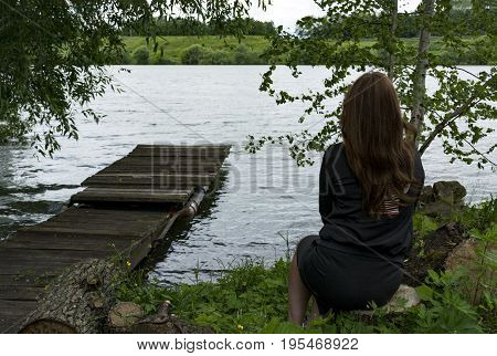 girl with long hair female one 1 sits on the banks of the river a wooden platform trees grass water