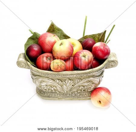 Fruit in a green vase. Vase with apples peaches plums and apricots