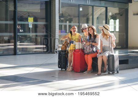 Cheerful girls at the airport waiting for flight. Young tourists briskly talk. In hands at girls of the passport and tickets. Summer vacation.